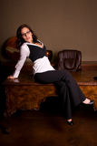 Seductive secretary. Full length shot of a sexy brunette business woman sitting on a wooden desk Royalty Free Stock Photography