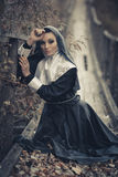 Seductive,sexual Nun Sits On The Wooden Bridge Outdoors And Pray For.Sexual Nun With Creative Make-up. Stock Image