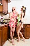 2 seductive sexy young pretty women in apron laughing in kitchen on white wall copy space background portrait Stock Images