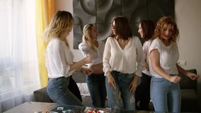 Seductive, young women on a hen party in identical casual clothes relaxed and dancing. Beautiful, modern interior stock video