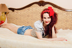 Seductive smiling young redhead woman lying on her Stock Image