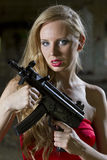 Seductive Spy with automatic gun. Gun woman in red dress with automatic gun in old fabric Royalty Free Stock Image