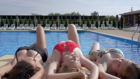 Seductive tanned girls lying on edge pool with perfect turquoise water on summer vacation. Seductive tanned girls lying on the edge pool with perfect turquoise stock footage