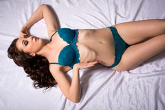 Seductive underwear model posing curved at camera Royalty Free Stock Image