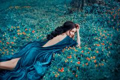 Seductive witch in a velvet blue robe resting in a clearing with yellow flowers. Long dark hair lying on a bare, open stock images