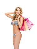 Seductive woman in bikini with shopping bags royalty free stock photo