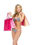 Seductive woman in bikini with shopping bags Stock Images