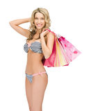 Seductive woman in bikini with shopping bags stock image