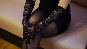 Seductive woman in dress, stockings and gloves stroke her leg. Seductive woman in short black dress, stockings and gloves stroke her leg stock video footage