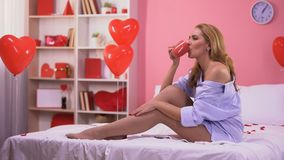 Seductive woman drinking hot coffee in bed, room decorated with heart balloons stock footage
