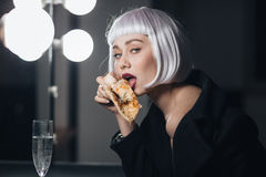 Seductive woman eating pizza and drinking champagne in dressing room Stock Image