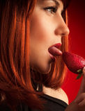 Seductive woman eating strawberry Royalty Free Stock Images