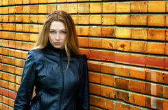 Seductive woman in front of brick wall. Seductive woman standing against brick wall Royalty Free Stock Image