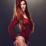 Seductive Woman Posing in Red Long Sleeved Leotard Royalty Free Stock Images
