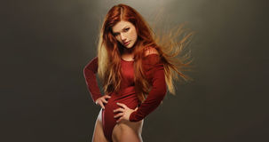Seductive Woman Posing in Red Long Sleeved Leotard Stock Photography
