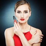 Seductive woman recommending lipstick and cosmetic products royalty free stock photo