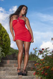 Seductive woman in red dress. A wonderfull South American model girl walks down the stairs of a park with a provocative and sensual attitude / the girl wearing a Stock Photo