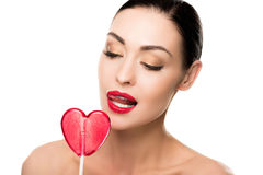 Seductive woman with red heart shaped lollipop licking her lips Stock Photography