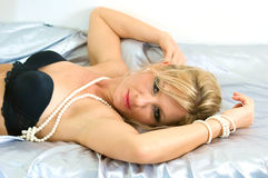 Seductive woman on satin royalty free stock photography