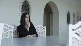 Seductive woman sits and poses at the table in luxurious home. stock video footage