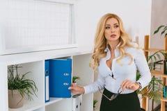 Free Seductive Woman Taking Folder From Shelf Stock Photos - 129235263