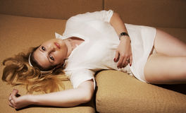 The woman lies on a sofa. Seductive woman in white shirt lying on the sofa Stock Photography