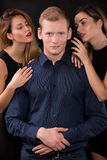 Seductive women tempting handsome man Stock Images
