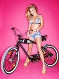 Seductive young blond on a bicycle Stock Photos