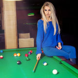 Seductive young blonde girl sits on pool table and looking at ca Royalty Free Stock Photography