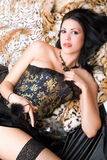Seductive young brunette in a corset. With bottle Royalty Free Stock Photos