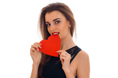 Seductive young brunette woman with red heart in hands posing isolated on white background. Saint Valentine`s day Stock Photo