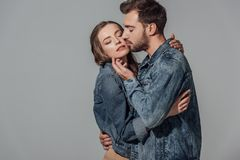 Seductive young couple with closed eyes embracing and touching each other. Isolated on grey Royalty Free Stock Images