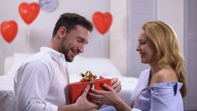Seductive young female giving red gift box to surprised boyfriend, anniversary. Stock footage stock footage