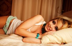 Seductive young female in lingerie lying on bed Stock Image