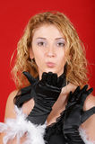 Seductive young girl blowing a kiss. Portrait of a beautiful young girl wearing black gloves with feathers and blowing a kiss toward the camera Stock Photography
