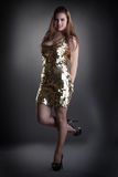 Seductive young girl posing in shiny golden dress Stock Photo