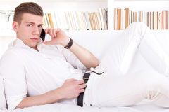 Seductive young man lying on sofa talking on the phone Royalty Free Stock Images