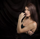 Seductive young woman biting chocolate candy Royalty Free Stock Photos