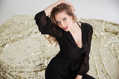 Seductive young woman in black dress sitting and posing Royalty Free Stock Image