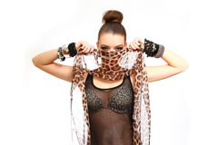 Seductive young woman hides her face with a leopard skin print i. Seductive young woman hides her face with a leopard skin print stock photos