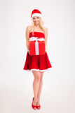 Seductive young woman in red santa claus dress and hat Stock Photo