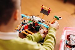 Sedulous boy dressed in green sweater sits at the table in the robotics school and makes a robot from the robotic. Constructor stock images