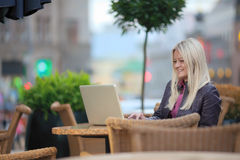 Seduta abbastanza bionda in caffè della via con il computer portatile Immagini Stock