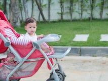 Seduta allegra asiatica sorridere e di sembrare della neonata in passeggiatore Fotografie Stock Libere da Diritti