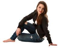 Seduta attraente della giovane donna isolata sopra fondo bianco Immagine Stock