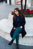 Seduta ben vestito del giovane studente sulla via con la sua compressa digitale Fotografie Stock