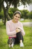 Seduta castana ispana sull'erba nell'yoga immagine stock