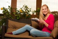 Seduta comoda della donna sul sofà e per mezzo del computer della compressa Fotografia Stock