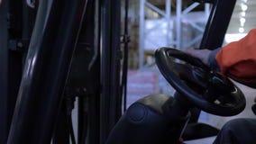 Seduta del caricatore dei controlli dell'operatore dietro la ruota che guida dopo gli scaffali con le merci in magazzino