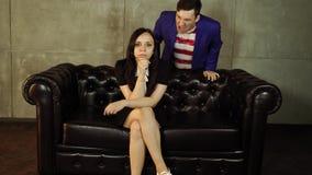 Seduta del maschio femminile e gridante Giovane donna spaventata in vestito nero che si siede sul sofà mentre uomo che prova a sp archivi video